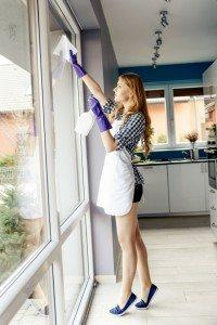 She is wearing a short white apron, and has purple protective rubber gloves on her hands. Washes a window in the living room