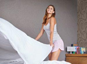 Cropped shot of an attractive young woman making up her bed